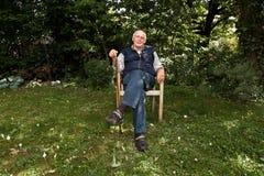 Homme plus âgé s'asseyant dans le jardin images libres de droits