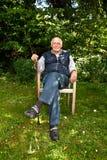 Homme plus âgé s'asseyant dans le jardin photo libre de droits
