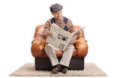 Homme plus âgé s'asseyant dans un fauteuil et lisant un journal Images libres de droits