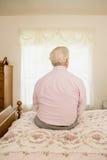 Homme plus âgé s'asseyant sur le lit photo stock