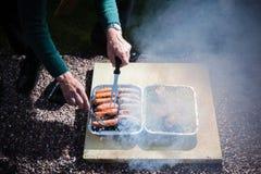 Homme plus âgé s'occupant le barbecue Photos stock