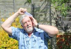 Homme plus âgé se peignant les cheveux Images stock