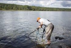 Homme plus âgé se tenant dans l'eau avec un marcheur et son filet de pêche essayant d'écoper les poissons Images stock