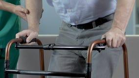 Homme plus âgé se tenant se tenant dessus sur le marcheur, infirmière l'aidant à faire des étapes banque de vidéos