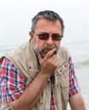 Homme plus âgé semblant triste sur la plage Image libre de droits