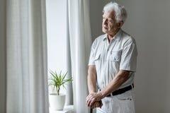 Homme plus âgé seul avec le bâton de marche se tenant prêt la fenêtre alo image stock