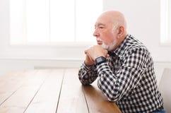 Homme plus âgé songeur s'asseyant à la table, l'espace de copie Photos stock