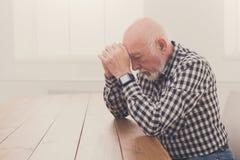 Homme plus âgé songeur s'asseyant à la table, l'espace de copie Photo libre de droits