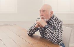 Homme plus âgé songeur s'asseyant à la table, l'espace de copie Photographie stock libre de droits