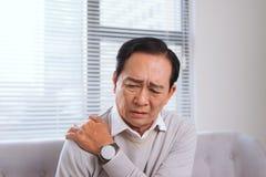 Homme plus âgé souffrant de la douleur d'épaule se reposant sur un sofa en Th Photos stock