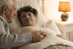 Homme plus âgé soutenant l'épouse malade Photo stock