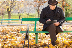 Homme plus âgé sur des béquilles utilisant une tablette Image stock