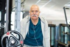 Homme plus âgé sur la machine de poids dans le gymnase Images stock