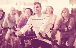 Homme plus âgé sur le cycle de forme physique dans le centre de fitness Photographie stock libre de droits