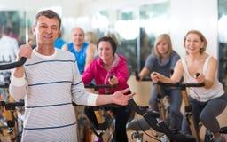 Homme plus âgé sur le cycle de forme physique dans le centre de fitness Image stock