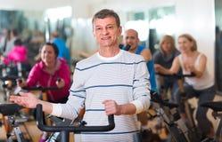 Homme plus âgé sur le cycle de forme physique dans le centre de fitness Photo stock