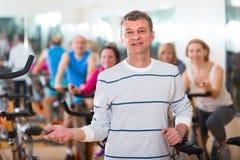 Homme plus âgé sur le cycle de forme physique dans le centre de fitness Photos libres de droits
