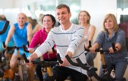 Homme plus âgé sur le cycle de forme physique dans le centre de fitness Photos stock