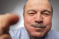 Homme plus âgé tenant à peine de retour le rire, soufflant ses joues Photos stock