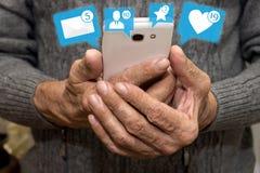 Homme plus âgé tenant le smartphone avec des icônes des avis du media social Media social pour le concept plus âgé Causerie avec  Photos libres de droits
