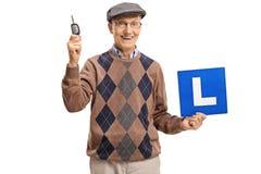 Homme plus âgé tenant une clé de voiture et un L-signe Photographie stock libre de droits