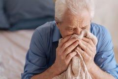 Homme plus âgé triste enterrant son visage dans sa veste de wifes Image libre de droits