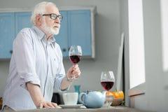 Homme plus âgé triste regardant dans la fenêtre Images stock