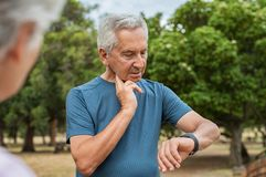 Homme plus âgé vérifiant l'impulsion après fonctionnement images stock