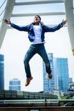 Homme plus fort asiatique sautant et courant avec le bâtiment et le citysc photo libre de droits