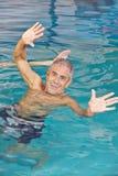 Homme plus âgé jouant la boule de l'eau dans la piscine Photographie stock libre de droits