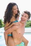Homme portant la femme gaie par la piscine Images stock