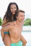 Homme portant la femme gaie par la piscine Photo stock