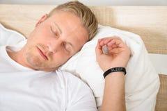 Homme portant le bracelet futé tout en dormant image stock
