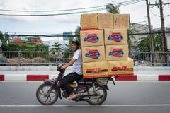 Homme portant les boîtes encombrantes sur une motocyclette Photographie stock