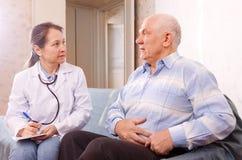 Homme portant plainte au docteur au sujet du mal de ventre images stock