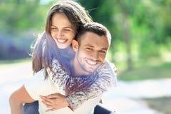 Homme portant son amie sur le dos rire heureux de couples Images libres de droits