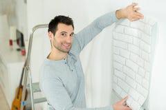 Homme posant tout en tenant le papier peint contre le mur photo libre de droits