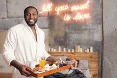 Homme positif d'Afro-américain tenant le plateau de petit déjeuner dans la chambre à coucher Photographie stock libre de droits
