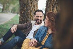 Homme positif et femme détendant sur l'herbe près de la route Photographie stock libre de droits