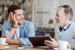 Homme positif et son grand-père se reposant ensemble dans le café Photos stock
