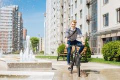 Homme positif joyeux montant sa bicyclette photos libres de droits