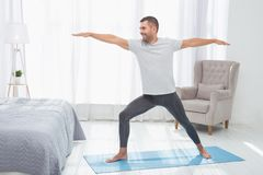 Homme positif joyeux se tenant sur un tapis de yoga photographie stock libre de droits