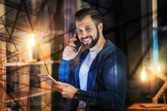 Homme positif parlant au téléphone avec son ami et sourire Photos libres de droits