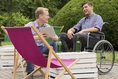 Homme positif sur le fauteuil roulant buvant avec l'ami Photos stock