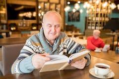 Homme potelé curieux lisant le livre intéressant en café photos stock