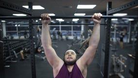 Homme potelé tirant vers le haut sur la barre, désir de perdre le poids et d'être fort, motivation banque de vidéos