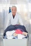 Homme poussant la blanchisserie de chariot photos libres de droits