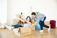 Homme poussant la femme s'asseyant dans la boîte en carton dans la nouvelle maison photos stock