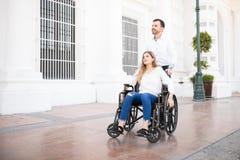 Homme poussant la femme sur un fauteuil roulant photos libres de droits