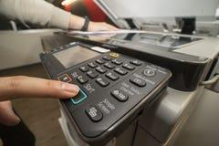 Homme poussant le bouton marche de l'équipement de photocopie pour le papier-copie de document images stock
